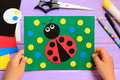 Child holds a summer card in his hands. Child made a paper ladybug card. Stationery on a wooden table. Easy paper circle crafts Royalty Free Stock Photo