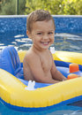 Child in home swimming pool happy toddler inflatable toy Stock Photography