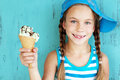 Child with ice cream portrait of years old kid girl eating tasty over blue Stock Photo