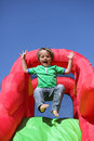 Child on inflatable bouncy castle slide year old boy jumping down the an Stock Photos