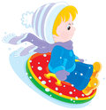 Child with an inflatable snow tube little boy or girl sitting in and sliding down Royalty Free Stock Images