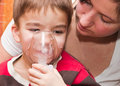 Child and inhaler european boy treated with a nebulizer Stock Photography