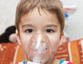 Child and inhaler european boy treated with a nebulizer Stock Image