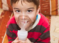 Child and inhaler european boy treated with a nebulizer Stock Photos