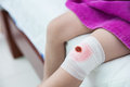 Child injured. Wound on the child's knee with bandage. Royalty Free Stock Photo