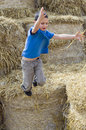 Child jumping in haystack boy playing hay from a Royalty Free Stock Image