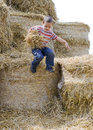 Child jumping in haystack boy playing hay from a Stock Images