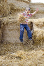 Child jumping in haystack boy playing hay from a Royalty Free Stock Images
