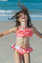 Child jumping for joy pretty little girl in swimsuit and laughing in excitement on a beach Stock Images