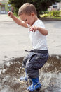 Child jumping in puddle Royalty Free Stock Photo