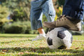 Child kicking the ball from fathers foot in park Stock Photo