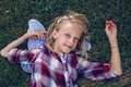 child kid girl with long hair wearing pink fairy wings and plaid shirt, lying on grass Royalty Free Stock Photo