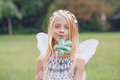 Child kid girl with long hair wearing pink fairy wings and tutu tulle skirt holding magic wand Royalty Free Stock Photo