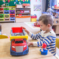 Child in kindergarden playing with toys at his desk Stock Image
