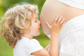 Child kissing belly of pregnant woman Royalty Free Stock Photo