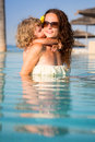 Child kissing woman in pool smiling women swiming summer vacations concept Stock Image