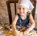 Child knead the dough in a kerchief pretty little girl having fun kneads Royalty Free Stock Image
