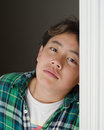 Child leaning on door frame half asian boy leans doorframe wearing a green plaid shirt Royalty Free Stock Photo