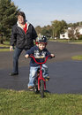 Child learning to ride bike a fit grandmother helps her grandson learn a Royalty Free Stock Photography