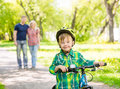 The child learns to ride a bike with his parents in the park