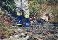 Child legs in gum boots into the forest creek Royalty Free Stock Photo