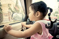 Child little girl looking the rain falling through the car window Royalty Free Stock Photo