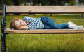Child little girl pleasure lying on bench in a park repose or relaxing in the nature Stock Image