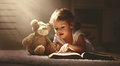 Child little girl reading a magic book in dark home Royalty Free Stock Photo