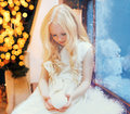 Child little girl with snowball toy over christmas tree bokeh home near window Royalty Free Stock Photo