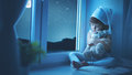 Child little girl at window dreaming and admiring the starry sky Royalty Free Stock Photo
