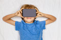Child liying in white bed with 3D Virtual Reality, VR cardboard glasses