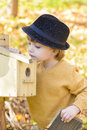 Child looking curious at one birds house in a forest in autumn time Stock Image
