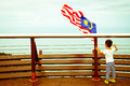 A child looks at malaysian flag view point of langkawi cable car in lankawi malaysia Stock Images