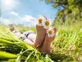 Child lying in meadow relaxing in summer sunshine with daisy between toes Royalty Free Stock Photos