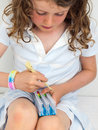 Child making a bracelet on a band loom small girl wearing braclet hooking elastic bands Royalty Free Stock Image