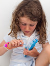 Child making a bracelet on a band loom small girl wearing braclet stretching elastic bands onto Royalty Free Stock Images