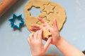 A child making cut-out cookies with cookie cutters on a blue table Royalty Free Stock Photo