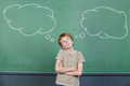 Child making a decision in school front of chalkboard with thought bubbles Royalty Free Stock Photography