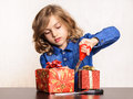 Child making present for christmas girl working at paper boxes using scissors scissor on table Royalty Free Stock Images