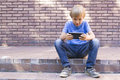 Child with mobile phone sitting outdoors. Boy looks at the screen, use application, plays. Sunny day. Brick wall Royalty Free Stock Photo