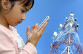 Child with mobile phone young girl using a cell tower as a backdrop Stock Photography