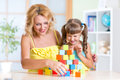 Child and mom playing wooden toys at home Royalty Free Stock Photo