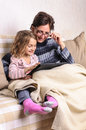 Child and mother using tablet on sofa Royalty Free Stock Photo