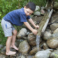 Child at nature water stream washing hands in with wooden fountain Royalty Free Stock Photography
