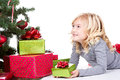 Child next to a christmas tree with presents with and isolated white background Stock Image