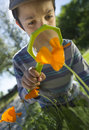 Child observing nature with a magnifying glass in garden Stock Photo