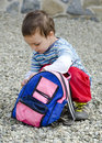 Child opening his bag small or toddler backpack or while crouching on the ground Royalty Free Stock Images
