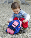 Child opening his bag small or toddler backpack or while crouching on the ground Royalty Free Stock Photo