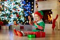 Child opening present at Christmas tree at home. Kid in elf costume with Xmas gifts and toys. Little baby boy with gift box and Royalty Free Stock Photo