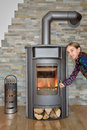 Child opening wood fired stove while burning Stock Images